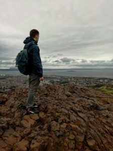 A boy looks at the sea of the Firth of Forth from the Arthur Seath, in Edinburgh