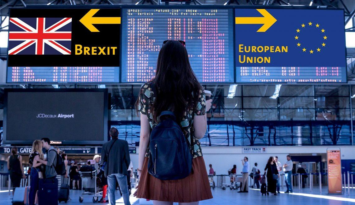 Una ragazza in aeroporto guarda al cartellone degli orari dei voli, dove spiccano due bandiere: Unione Europea e UK con frecce che puntano in due direzioni diverse in relazione della Brexit