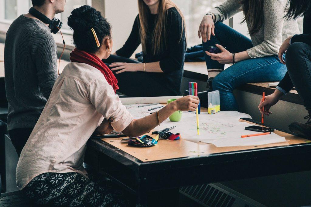 Un gruppo di studenti di culture diverse seduti attorno a un tavolo per discutere di un progetto erasmus universitario.