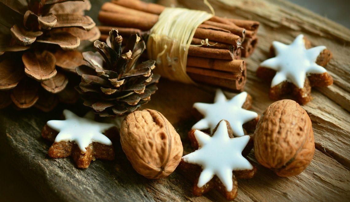 Foto di noci, pigne, zenzero, cannelle e biscotti natalizi su di un tavolo di legno.
