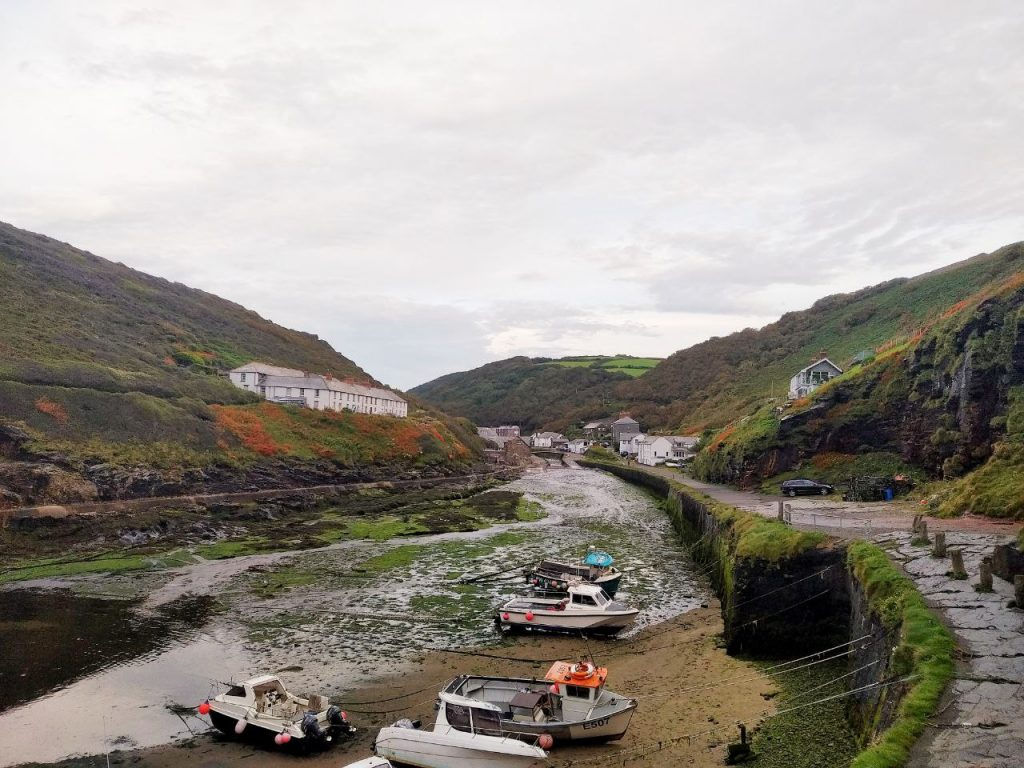 Vista del porto al villaggio di Boscastle alla bassa marea, con barche arenata e gli edifici tra le verdi colline della cornovaglia