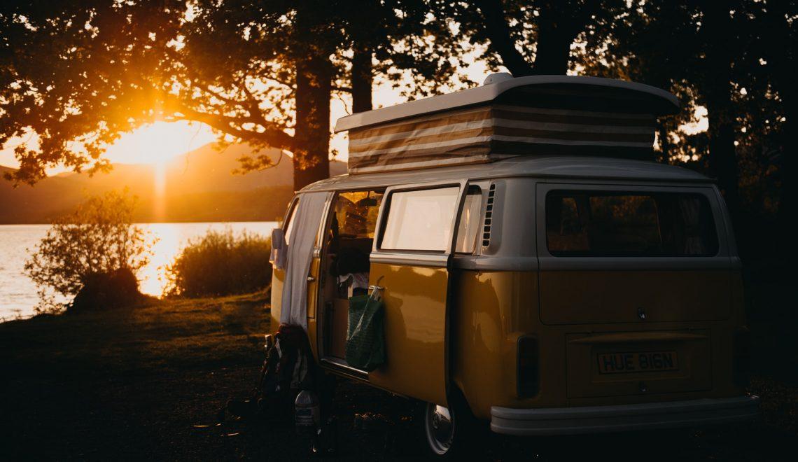 Un caravan parcheggiato sotto un albero al tramonto.