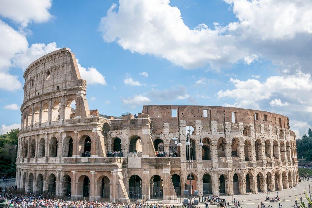 Il Colosseo in una giornata di sole, con il cielo azzurro e le nuvole.