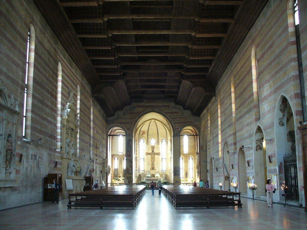 L'interno della Chiesa degli Eremitani a Padova, con le panche in legno, il pavimento in marmo e il crocifisso centrale.