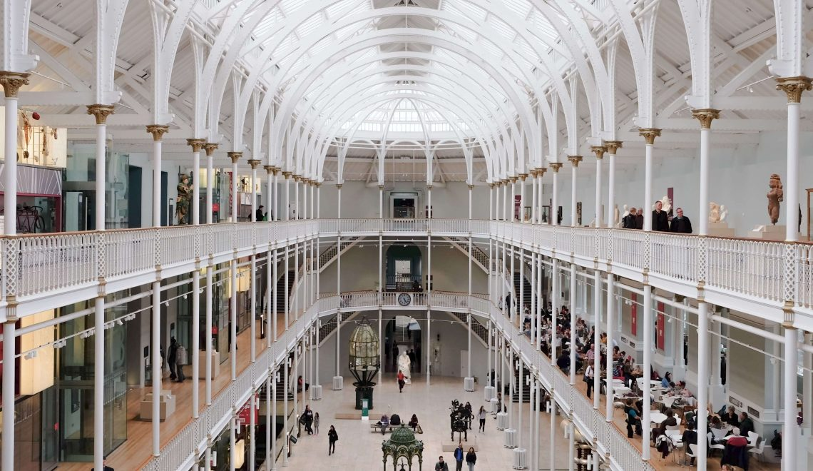Gli interni del Museo Nazionale di Scozia, suddiviso in tre livelli con le ringhiere biance e le alte arcate in metallo, anch'esse bianche, che sostengono una cupola in vetro.