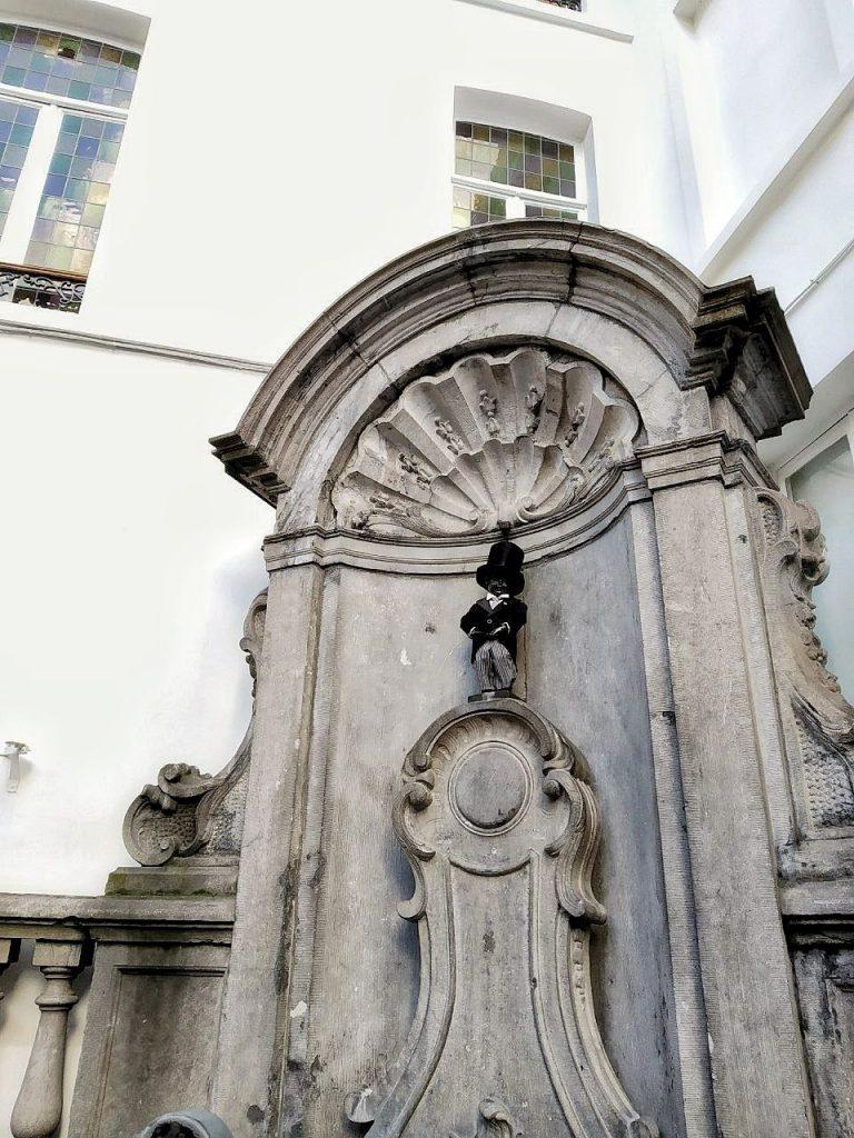 La fontana di Mannekken Pis vestito da damerino con lo smoking e la tuba.