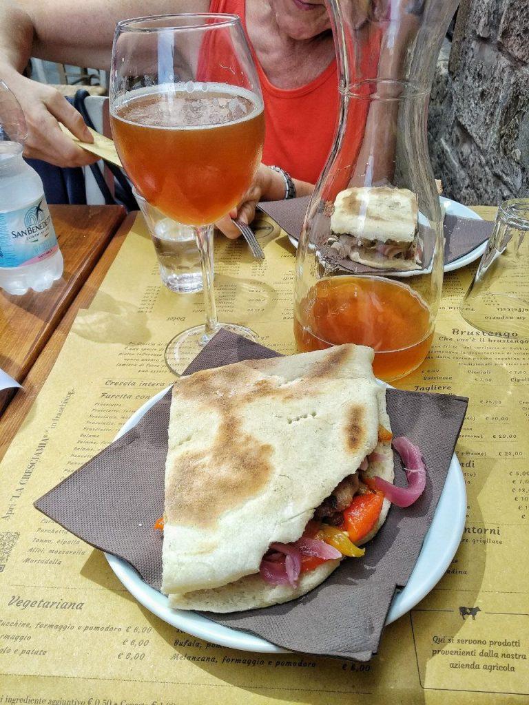 Un fantastico piatto di Crescia con peperoni, cipolla rossa, carne e un bicchiere di birra Umbra.