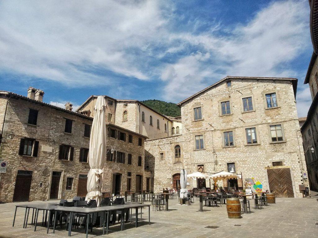Piazza Bosone a Gubbio, una piccola piazzetta con palazzi storici in sasso e tavolini con ombrelloni di bar all'esterno.