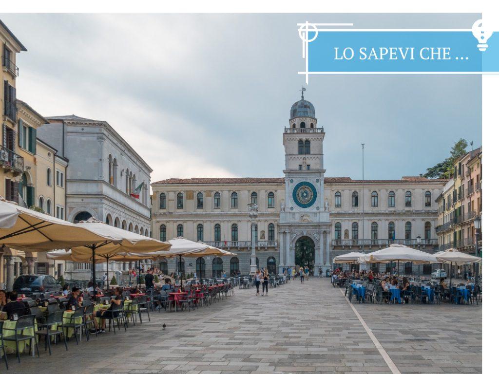 L'orologio astronomico di Piazza dei Signori a Padova, con i tavolini coperti da ombrelloni al centro della piazza.
