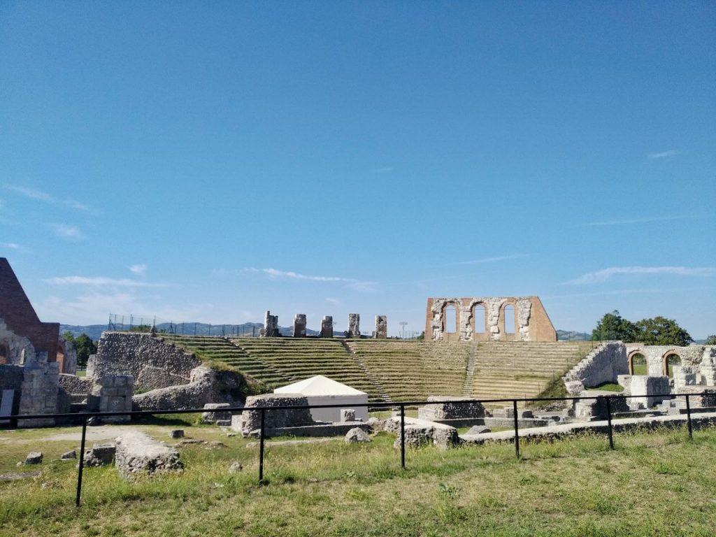 I resti dell'antico teatro romano a Gubbio, con qualche arcata e tante scalinate in semicerchio.