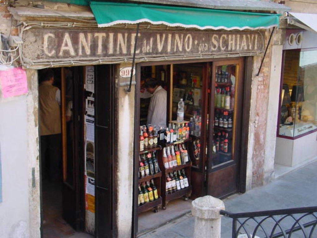 """La vetrina del bacaro """"Cantine del Vino gia Schiavi"""" a Venezia, con bottiglie di vino in vista."""