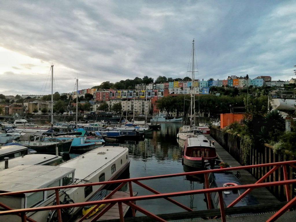 Il porto di Bristol, dove molte navi sono ormeggiate e da cui si vedono le colorate case sulla collina.