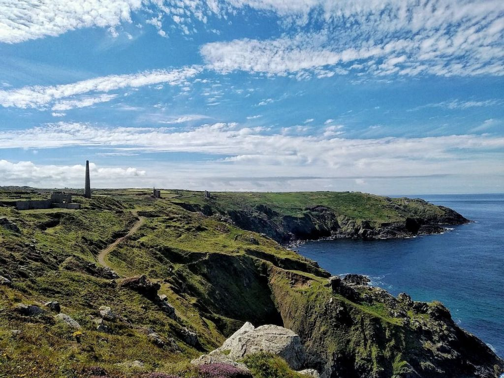 Vista della costa della Cornovaglia sull'oceano, con qualche miniera d'acciaio sparsa.
