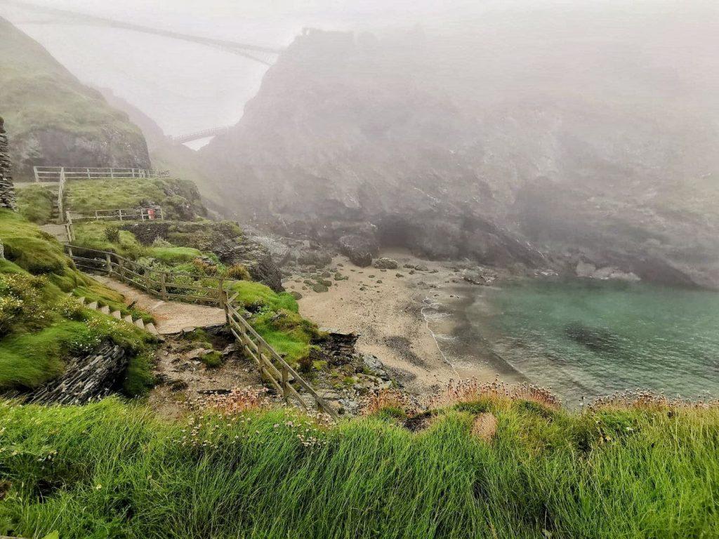 Vista del castello di Tintagel e della piccola spiaggia durante una giornata di nebbia.