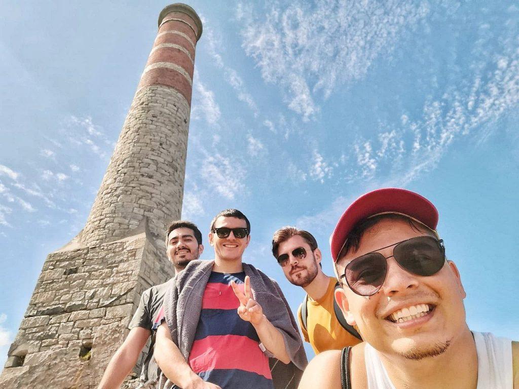 Quattro ragazzi fanno un selfie con una torre delle miniere della Cornovaglia.