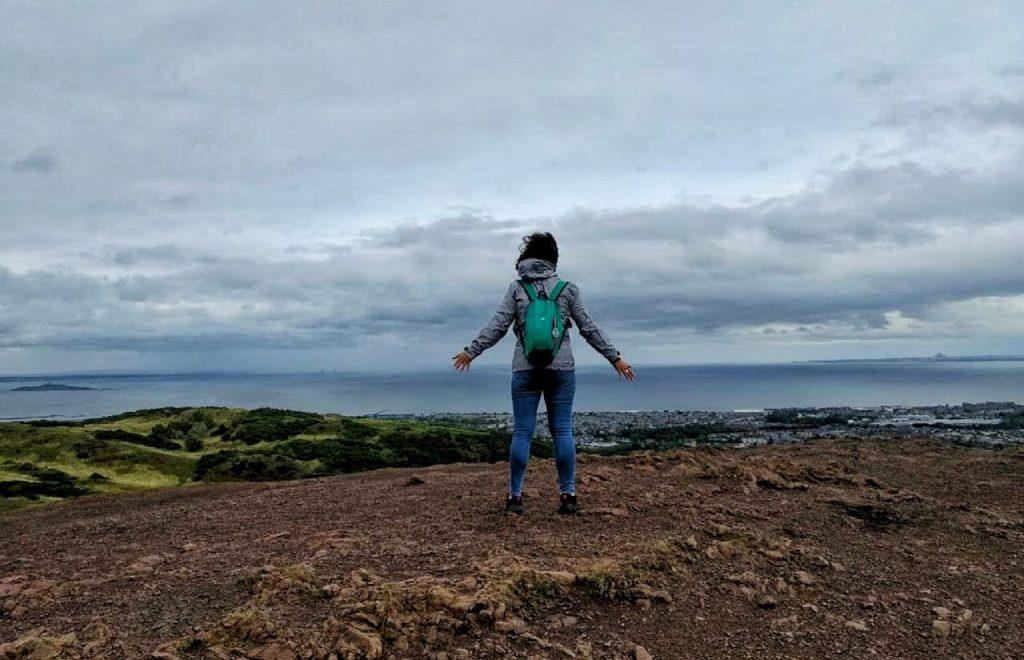 Una ragazza in piedi di spalle con braccia e gambe aperte sulla cima dell'Arthur Seath, con vista sulla città di Edimburgo e sul mare in lontananza.