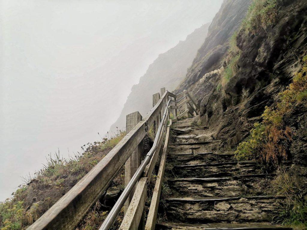 La lunga scalinata in sasso, affiancata dalla roccia, che conduce al castello di Tintagel, in Cornovaglia.