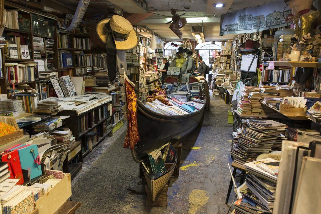 L'interno della libreria Acqua Alta a Venezia, con libri e mappe sparsi ovunque, anche dentro una gondola.