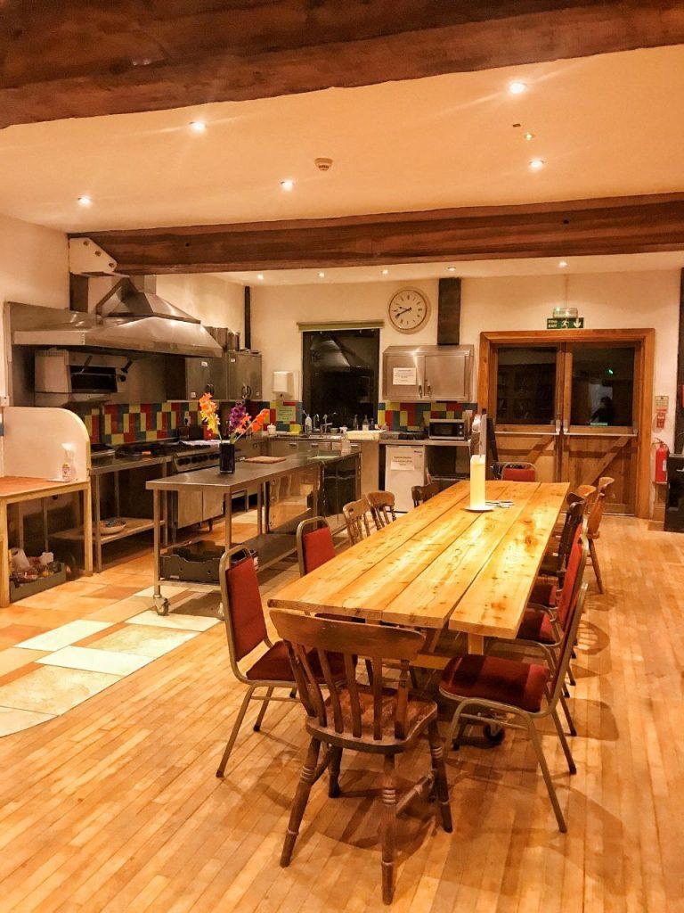 Il salone interno di una cucina interno, con un tavolo enorme e dei grandissimi piani cottura.