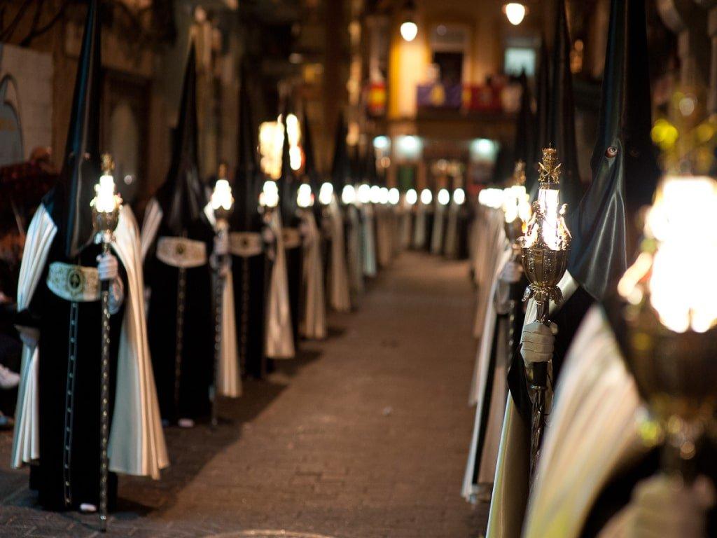 Un gruppo di uomini incappucciati di nero portano in mano delle torce. Rappresentano i Nazarenos, durante la processione pasquale in Spagna.