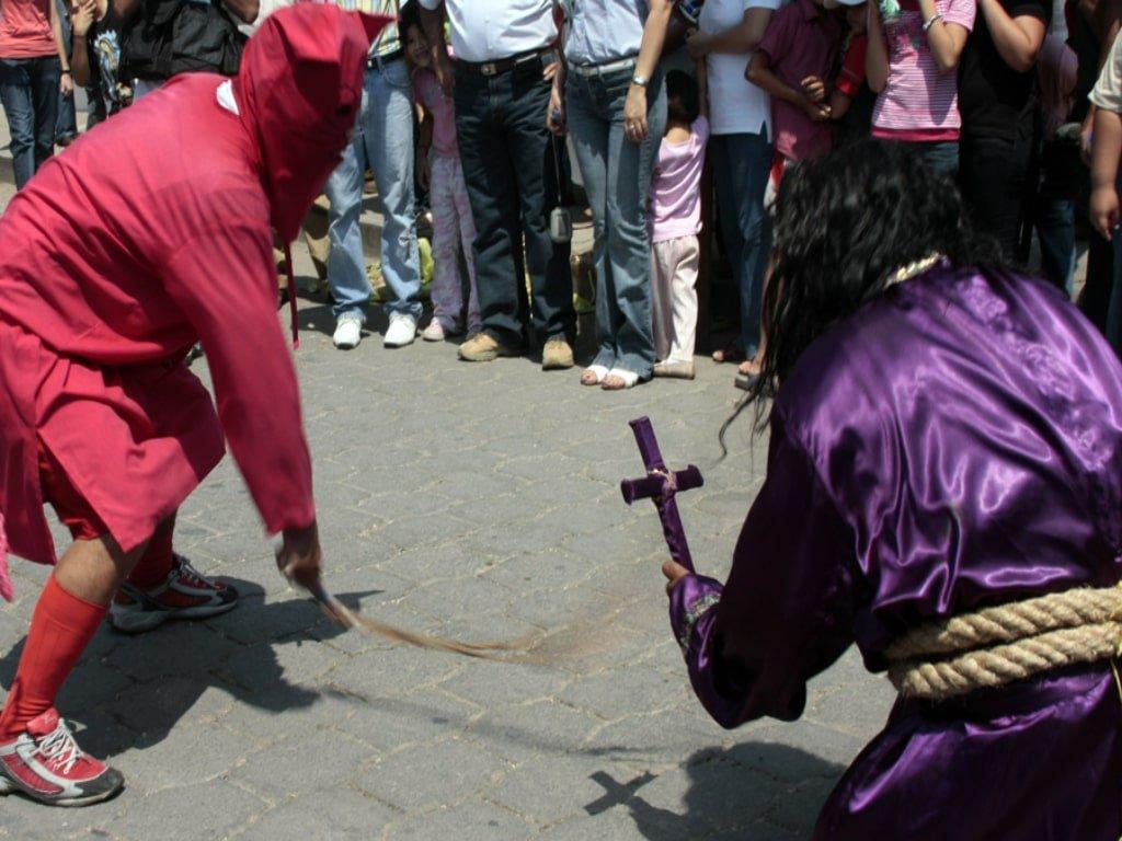 Due uomini vestiti di rosso e di viola rappresentano un Talciguine e un monaco durante la celebrazione di Pasqua a El Salvador.