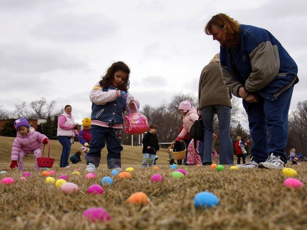 Bambini e adulti raccolgono uova colorate da terra.