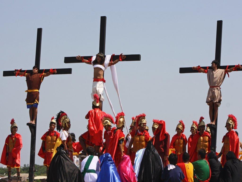 Una folla osserva la riproduzione della crocefissione di Gesù e dei criminali da parte dei romani in una ricostruzione pasquale nelle Filippine