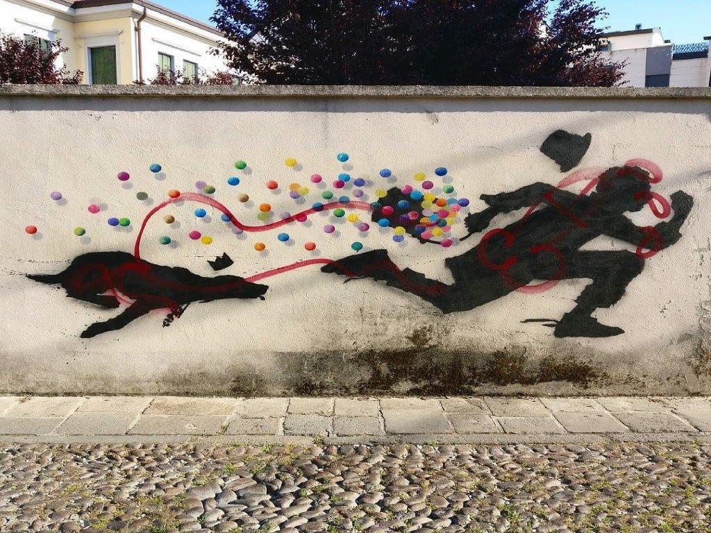 Un'opera d'arte di Kenny Random a Padova raffigurante un uomo con un cane che corre con palline colorate sullo sfondo