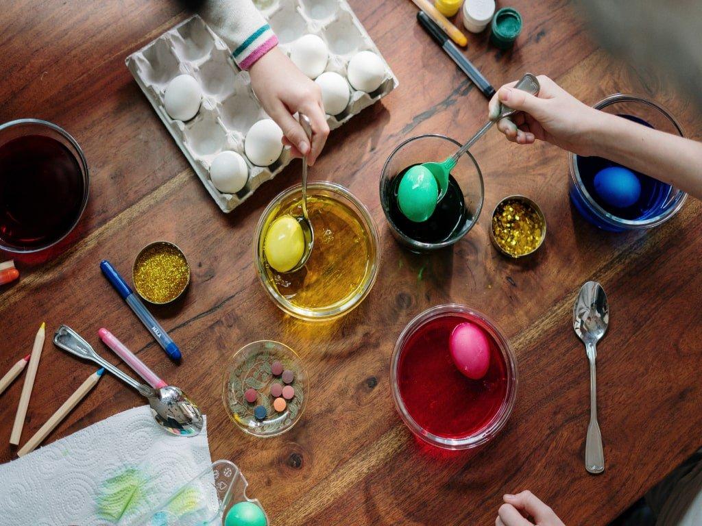 Due ragazze decorano delle uova con colori e brillantini.