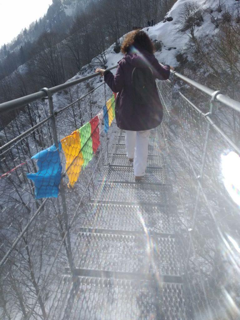 Una ragazza attraversa il ponte tibetano di Valli del Pasubio.