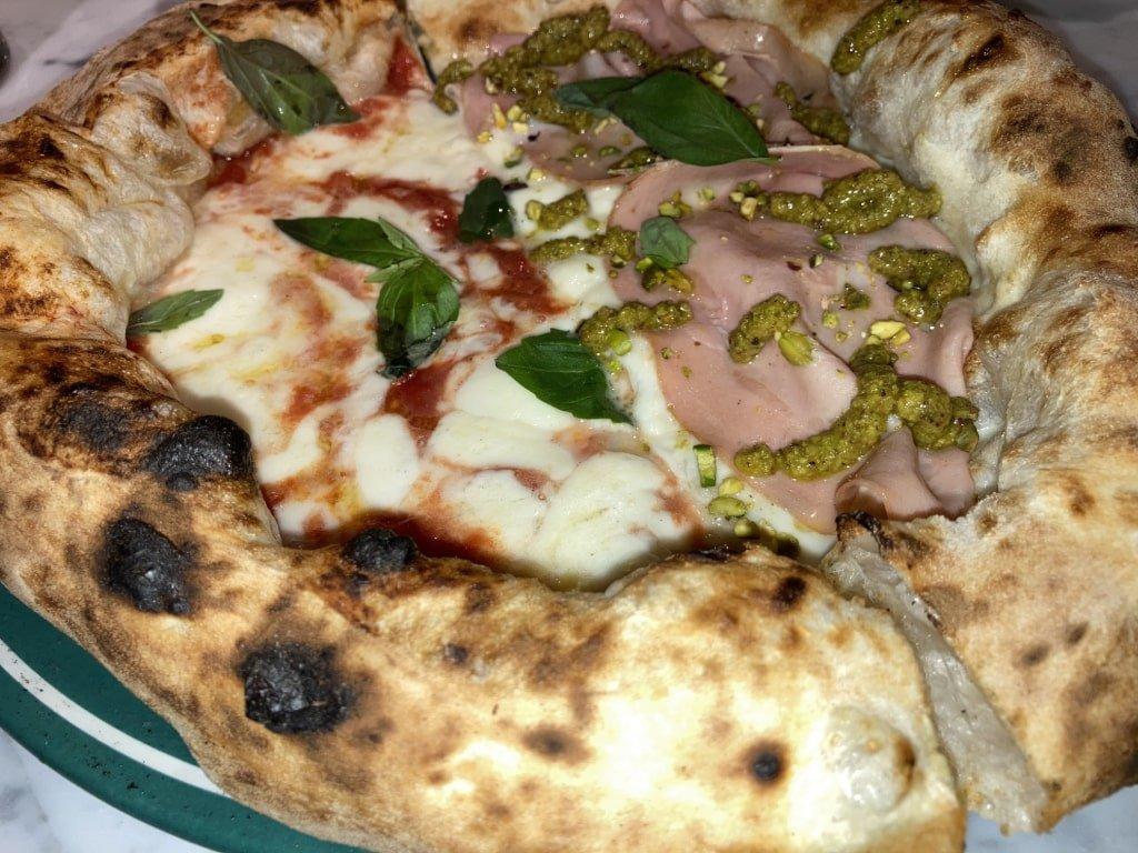 La deliziosa pizza di Vincenzo Capuano a Pozzuoli: mezza margherita e mezza con mortadella e pistacchi nello stesso piatto.