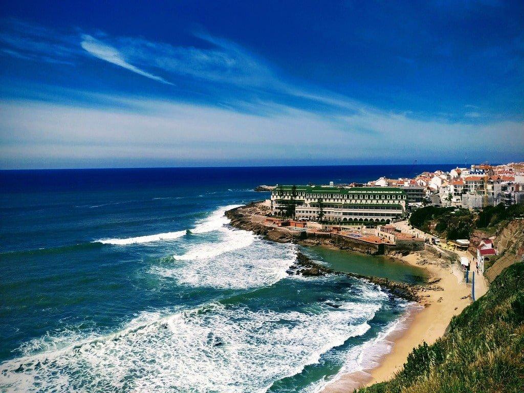 Vista del porto di Ericeria in Portogallo, con la sua spiaggia dalla sabbia dorata e l'oceano di un blu intenso.