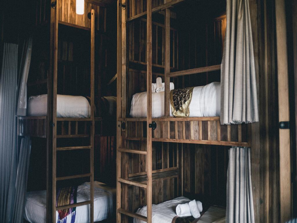 I letti in legno con lenzuola bianche di una camera di ostello.
