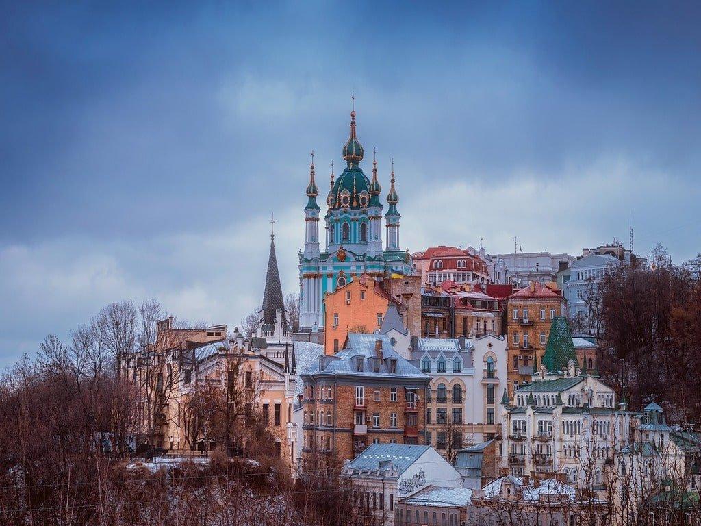 Vista dela Cattedrale blu di Kiew e delle sue case colorate da un parco.