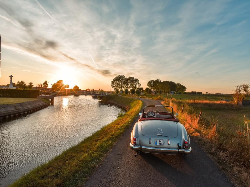 Un'auto d'epoca lungo un fiume e viaggia verso il tramonto.