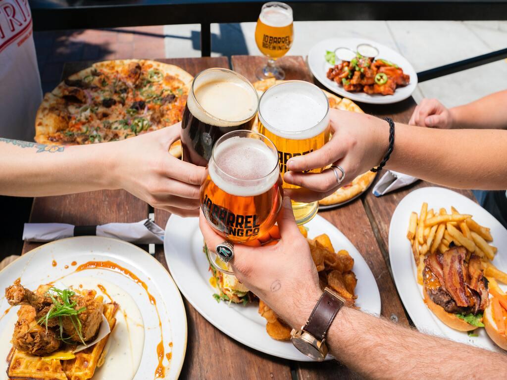 Persone fanno un brindisi con delle birre su un tavolo con cibo.