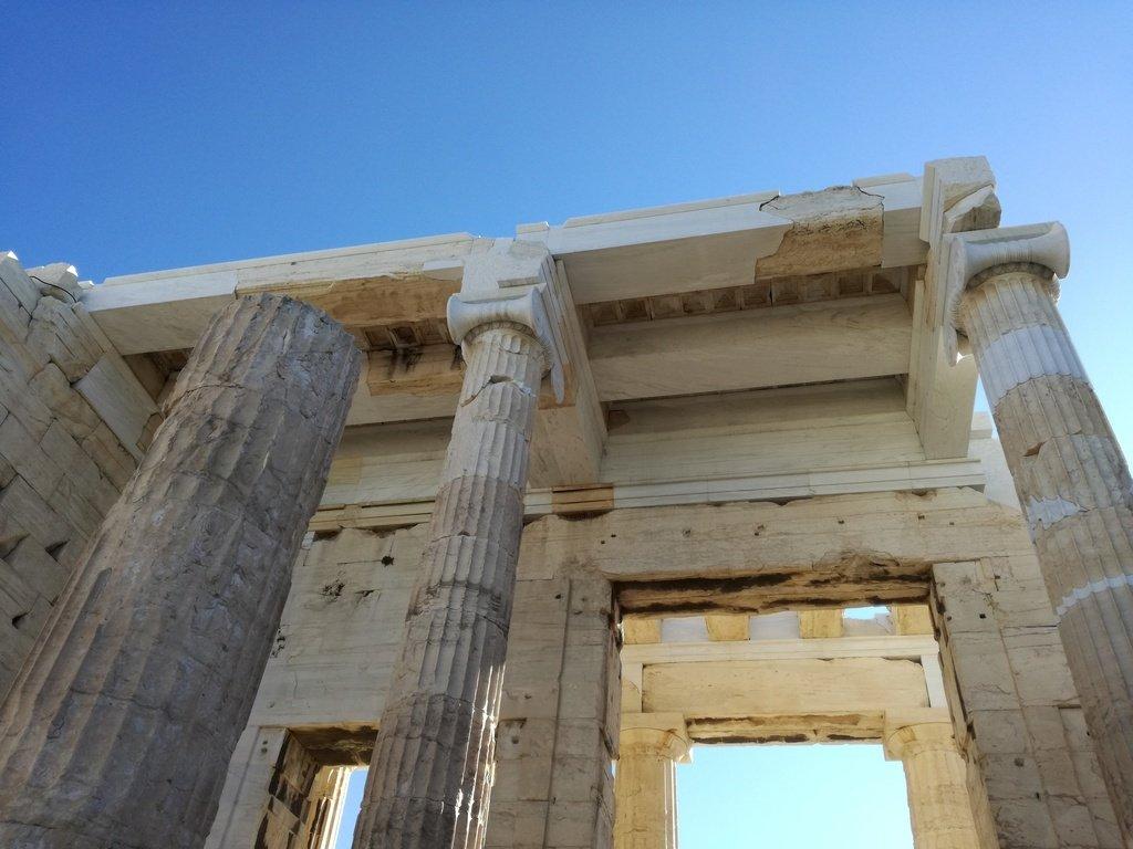 Tempio greco in marmo con colonne e ingresso verso sito archeologico