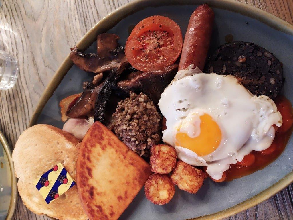 Un piatto contenente una colazione alla scozzese con uova, salsicce, haggis, bacon, pomodori e pane