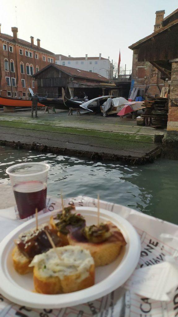 Un paiatto con tapas e un bicchiere di vino di fronte allo Squero San Trovaso di Venezia