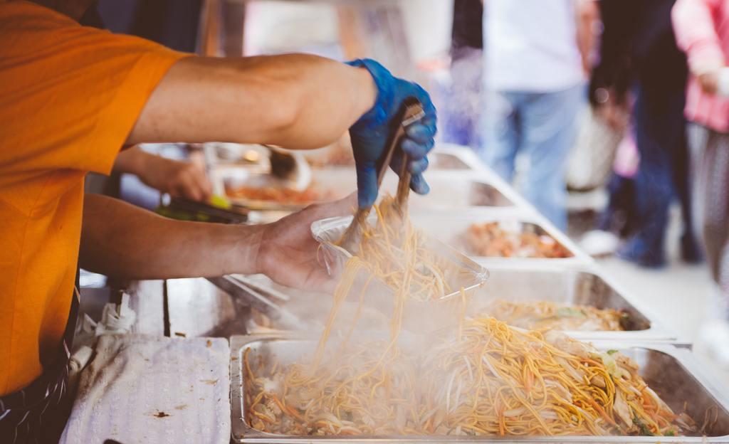 Un uomo sta riempendo una vaschetta di alluminio con noodles precotti in un banchetto di street food.