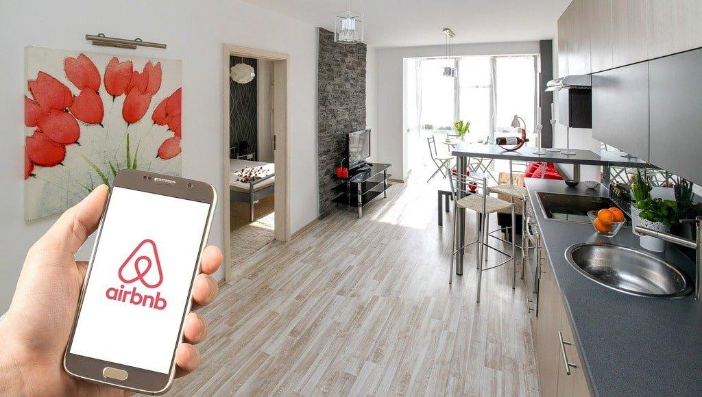 Una mano tiene un telefono davanti a una cucina ordinata e moderna.