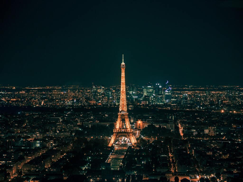 La torre Eiffell e la capitale francese di Parigi illuminati di notte.