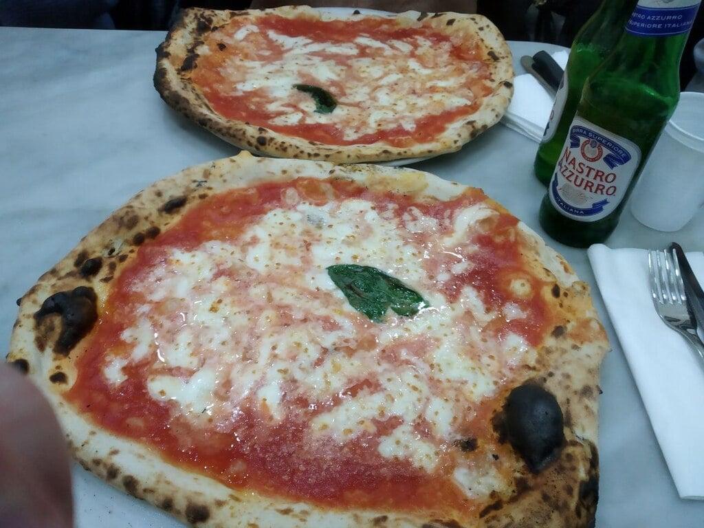 Due deliziose pizze margherite con due bottiglie di birra peroni nella pizzeria Da Michele