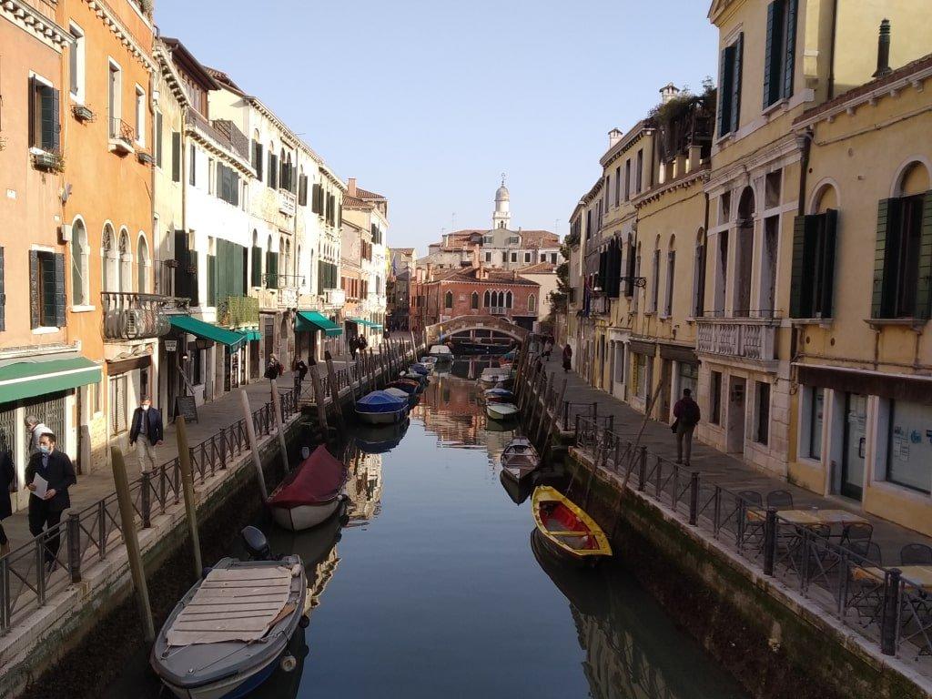 Uno dei tanti canali di Venezia con barche e negozi ai lati