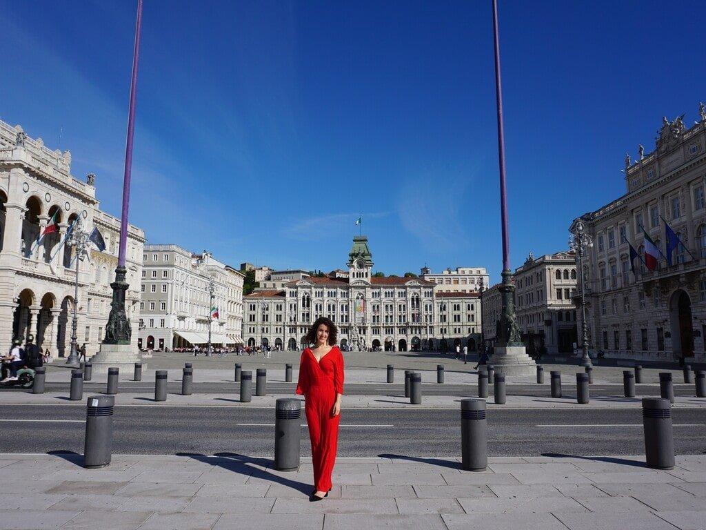 Una ragazza col vestito rosso davanti a Piazza Unità d'Italia a Trieste