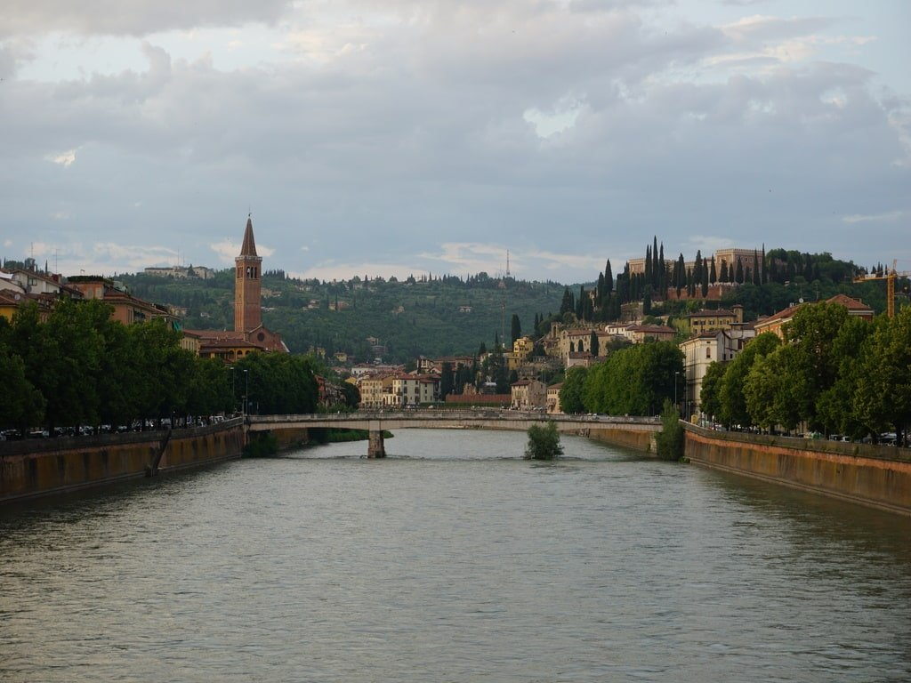 a bridge on the river in the city centre with hills and bell tower and castle on the hill