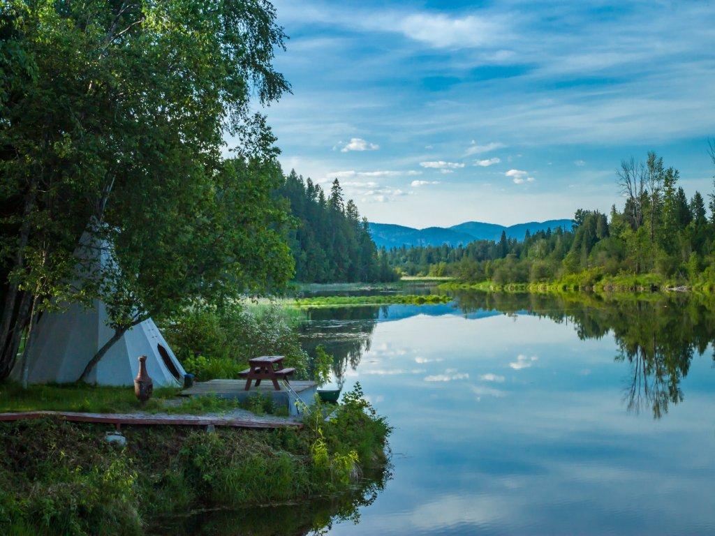Una tenda bianca in stile indiano si trova sul bordo di un fiume, con sullo sfondo alberi e montagne in lontananza.