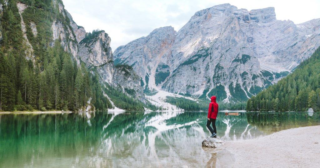 Un ragazzo col giubbino rosso osserva le montagne specchiarsi sul Lago di Braies in Trentino Alto Adige