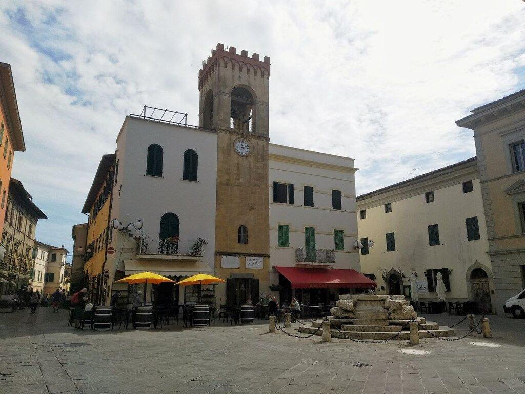 Una piazzetta su cui affaccia un bar e una torre campanaria con orologio a Casiglione del Lago