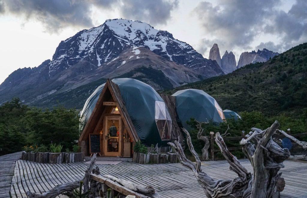 Delle capanne di legno e vetro tra un bosco verde con vista sulle alpi.